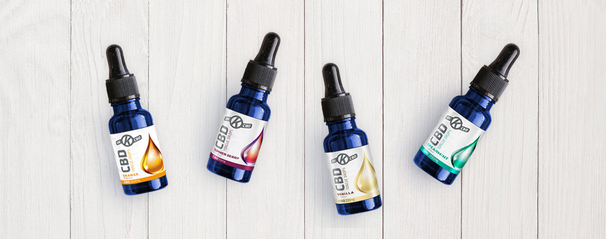 OK CBD Bottles on white wood background